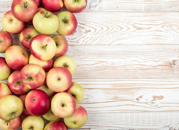 ジュースの準備ができている全体の赤と緑のソフトアップルパターンは、上面図を生成します。木製の素朴な表面に有機リンゴ