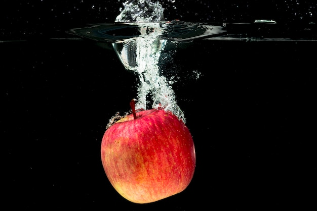 Whole red apple falling in water over black background