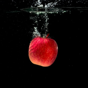 Whole red apple splashing in water against black background