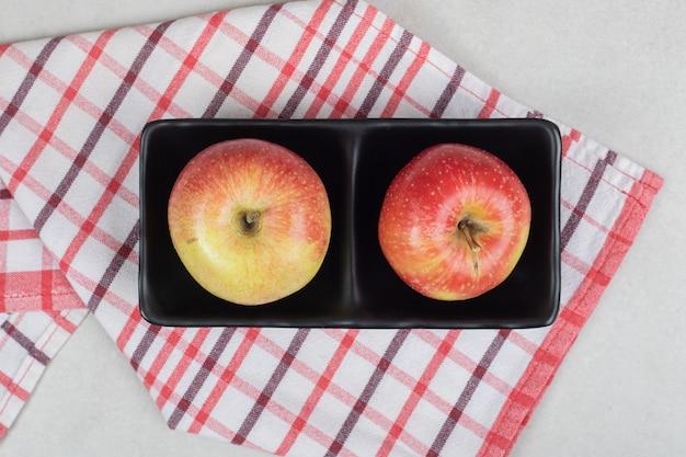 식탁보와 함께 검은 접시에 전체 빨간 사과