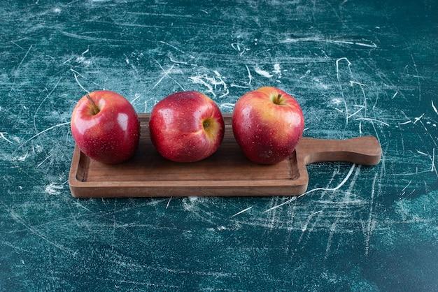 Mele rosse intere sulla tavola di legno.