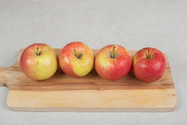 Whole red apples on wooden board