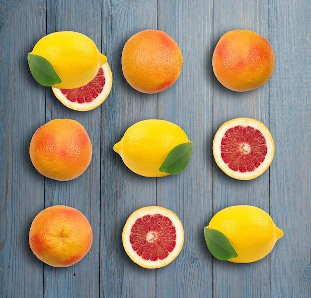 木製の表面のクローズアップにオレンジの皮と全体の赤いグレープフルーツ。ジューシーなほろ苦いフルーツのセクション。ルビーシトラスとレモンパターン