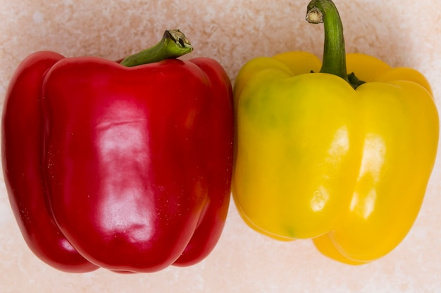 Whole red and yellow bell peppers on textured backdrop