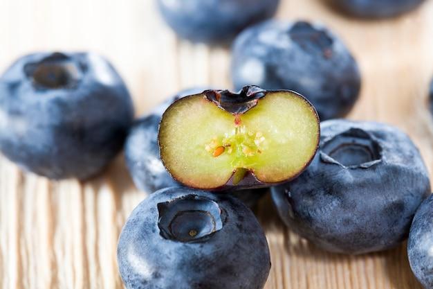 완전히 익고 맛있는 블루 베리 열매는 야생의 건강한 블루 베리 열매, 근접 촬영 및 음식 세부 정보의 절단 열매와 함께 나무 테이블에 놓여 있습니다.