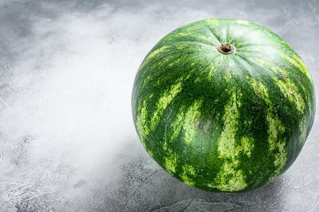 丸ごと熟した緑のスイカ。灰色の背景。上面図。コピースペース。