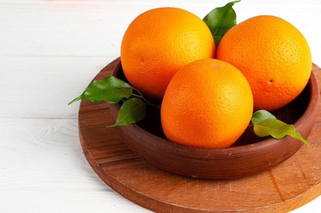 白いテーブルの上の粘土のボウルに完全に熟したオレンジ