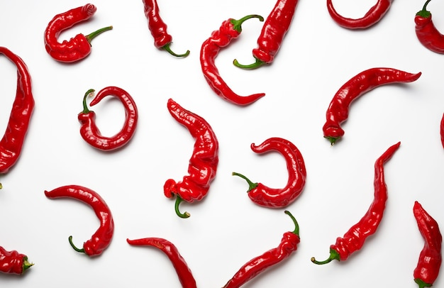 Whole ripe red hot pepper scattered background