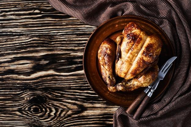 전체 로스트 치킨은 갈색 천, 포크 및 나이프, 평평한 바닥, 클로즈업, 여유 공간, 위에서 가로보기가있는 나무 테이블에 토기 접시에 제공됩니다.