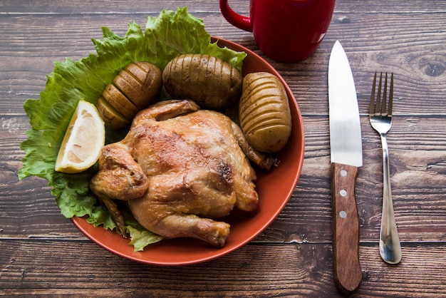 Whole roasted chicken in bowl with potato; knife and fork on wooden table
