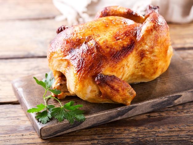 나무 보드에 완전히 구운 된 닭