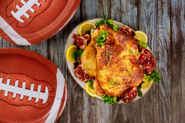 Whole roasted chicken on plate with salad and pomegranate for american football party