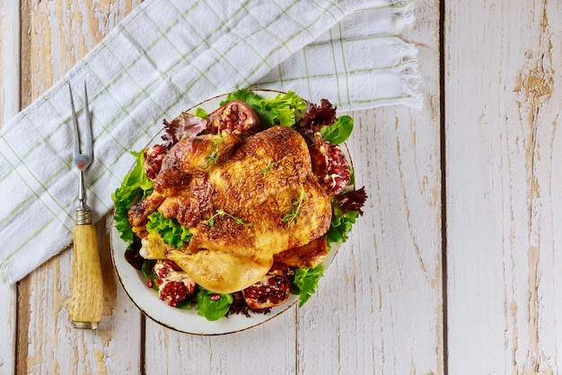 Whole roasted chicken on plate with salad, pomegranate and fork