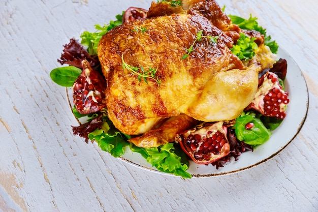 Whole roasted chicken on plate with salad and pomegranate