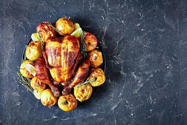 콘크리트 테이블에 구운 사과와 아로마 허브와 함께 검은 접시에 완전히 구운 치킨 제공