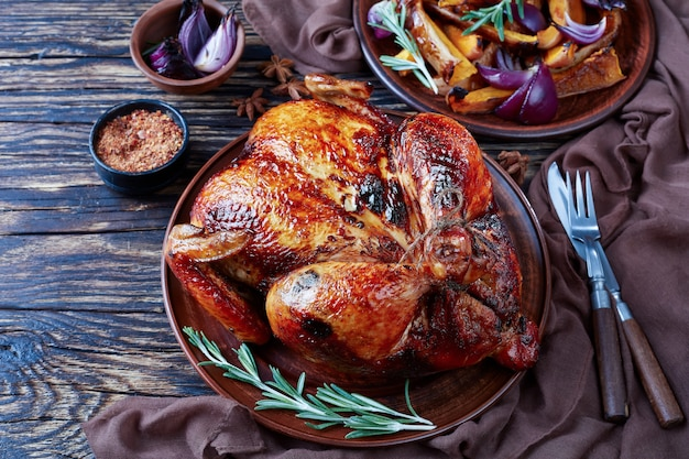 Whole roasted chicken with golden brown crispy skin served on a earthenware dish with caramelized grilled pumpkin slices and grilled red onion, view from above, close-up