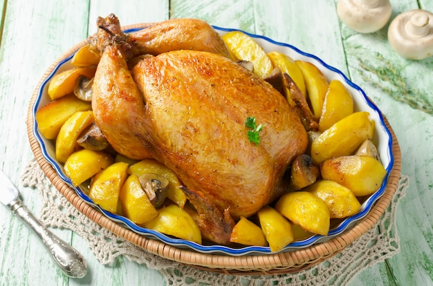 Whole roasted chicken with potatoes and mushrooms