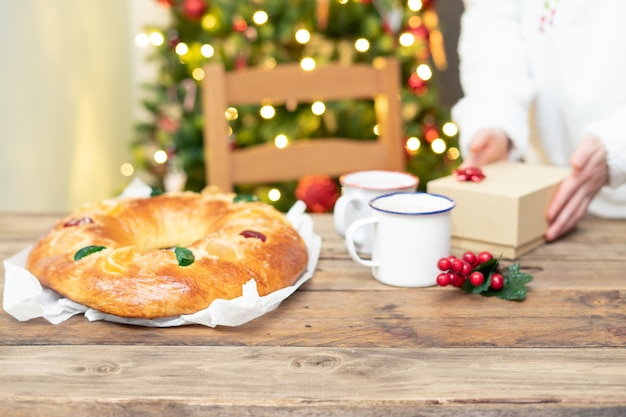 Whole roscã³n de reyes on wooden table with christmas tree in the background. christmas sweets.