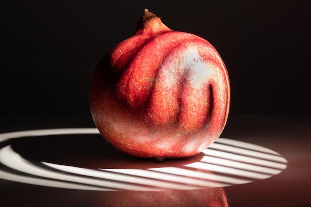 A whole scarlet pomegranate on a black background close-up.