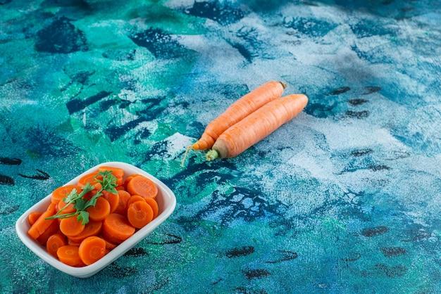 Carote intere e affettate con prezzemolo in una ciotola, sul tavolo blu.