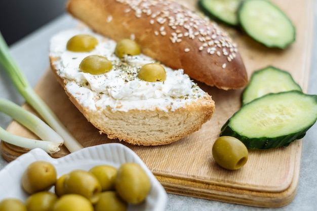 Whole and slice of homemade bread on a wooden board with cream cheese and olives in bowls.