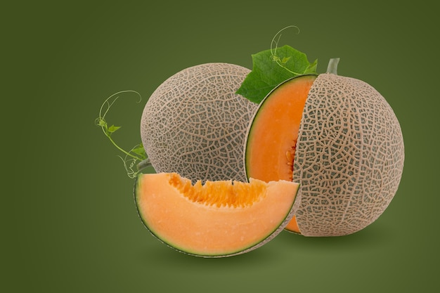 Whole and slice of japanese melons, orange melon or cantaloupe melon with seeds isolated on green background