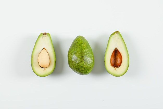 Whole and sliced avocado on a white surface. top view.
