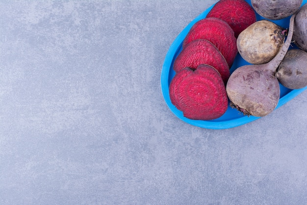 Whole and sliced beetroots in a blue platter
