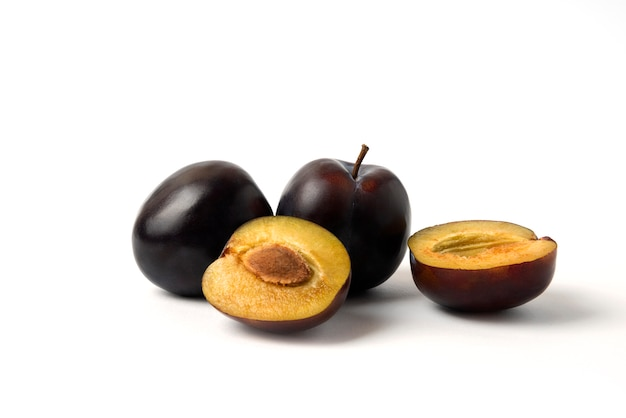 Whole and sliced black cherry plums on the white table
