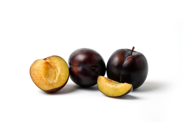Whole and sliced black cherry plums