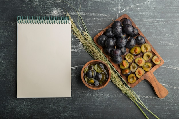 Whole and sliced black plums on a wooden board with a receipt book aside