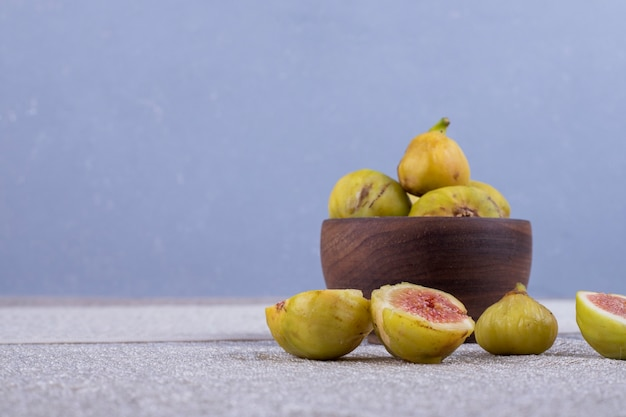 Whole and sliced figs in a wooden bowl and on the white table.
