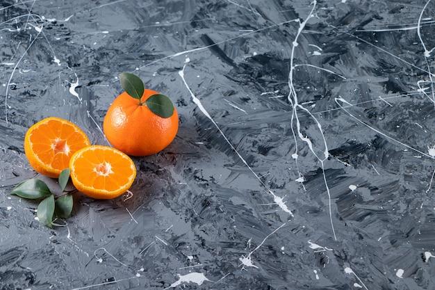 Frutti di arancia freschi interi e affettati con foglie poste su una superficie di marmo