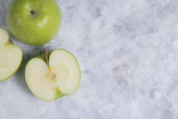Frutti interi e affettati di mela verde matura fresca posizionati su uno sfondo di marmo. foto di alta qualità