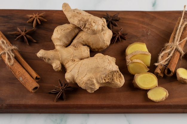 Whole and sliced ginger on a piece of wood.