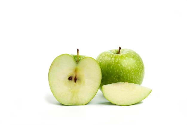 Whole and sliced green apples isolated on white.