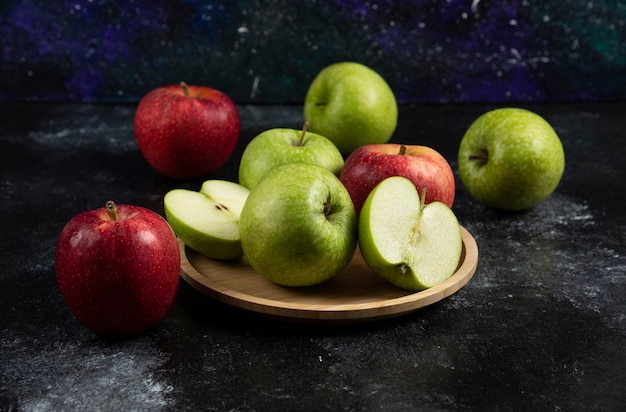Whole and sliced green and red apples on wooden plate.