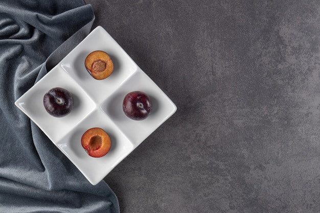 Whole and sliced juicy red plum fruits placed on a white plate.