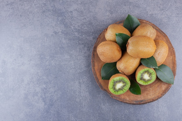 Whole and sliced kiwi fruit placed on a stone table.