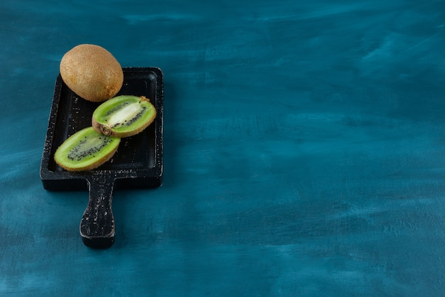 Whole and sliced kiwi fruits placed on a dark wooden board.