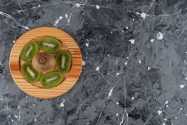 Whole and sliced kiwi fruits placed on a wooden board.