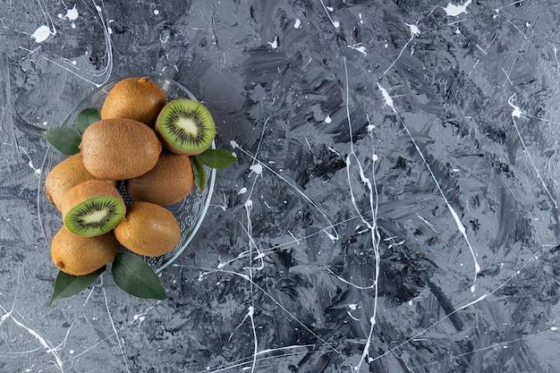 Kiwi interi e affettati con foglie poste in una tavola di vetro.