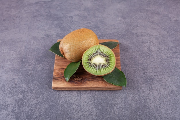 Whole and sliced kiwi fruits with leaves placed on a stone .