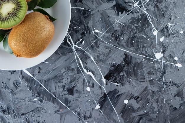 Kiwi interi e affettati con foglie poste in un piatto bianco.