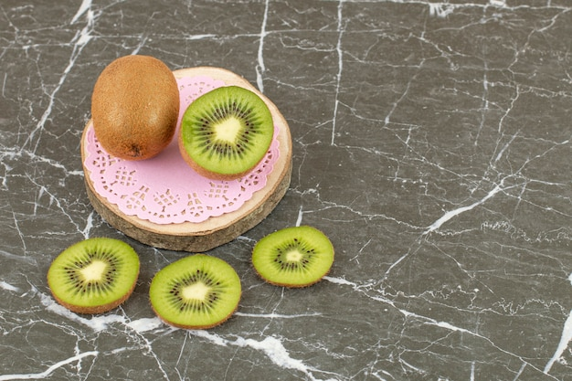 Whole and sliced kiwi on wooden board.