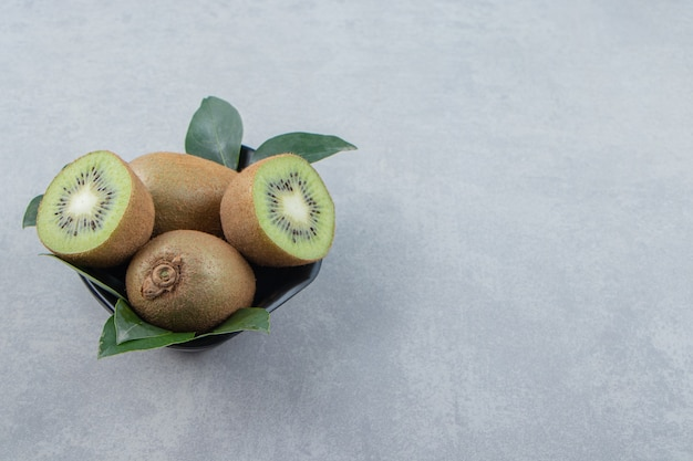 Whole and sliced kiwis in black bowl
