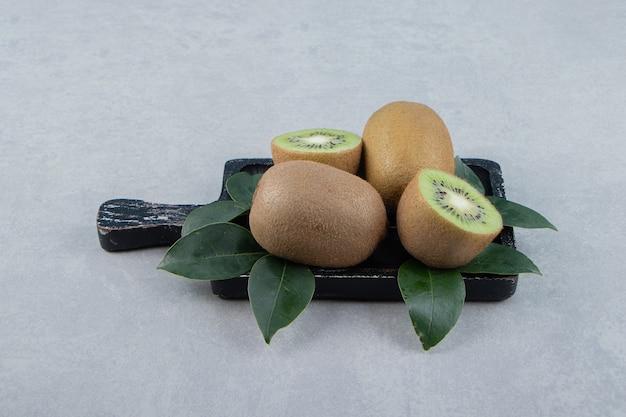 Kiwi interi e affettati sul tagliere nero.