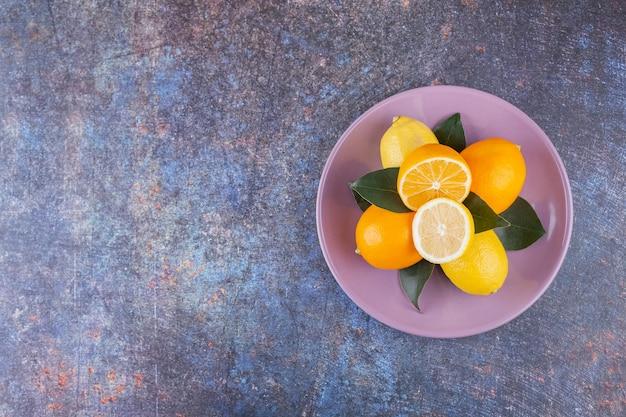 Whole and sliced lemon fruits placed on a stone .