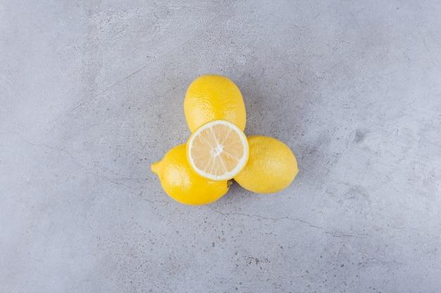 Frutti di limone interi e affettati con foglie poste sul tavolo di pietra.