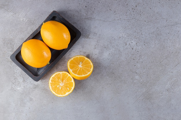 Whole and sliced lemons placed on black board